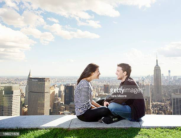 man and woman smiling next to city skyline