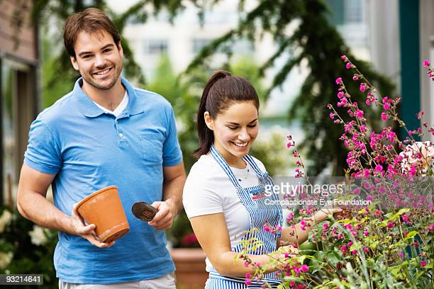 "man and woman smiling while working outside - ""compassionate eye"" fotografías e imágenes de stock"