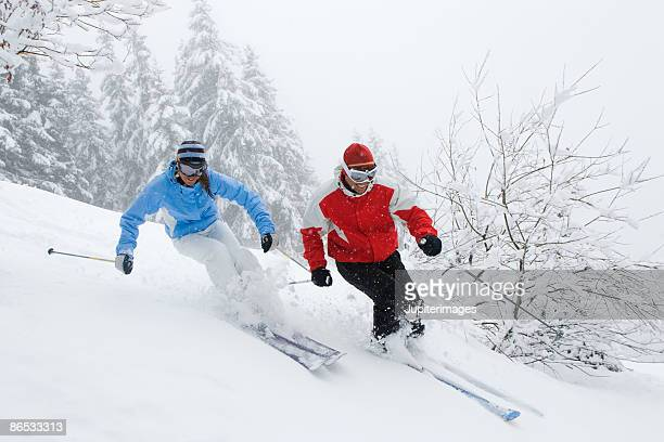 man and woman snow skiing - downhill skiing stock pictures, royalty-free photos & images