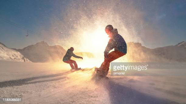 man and woman snowboarding on mountain - snowboarding stock pictures, royalty-free photos & images