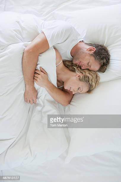 man and woman snuggling in bed asleep - heterosexual couple stock pictures, royalty-free photos & images