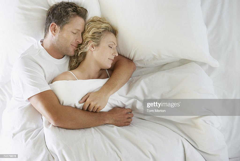 Man and woman snuggling in bed asleep : Stock Photo
