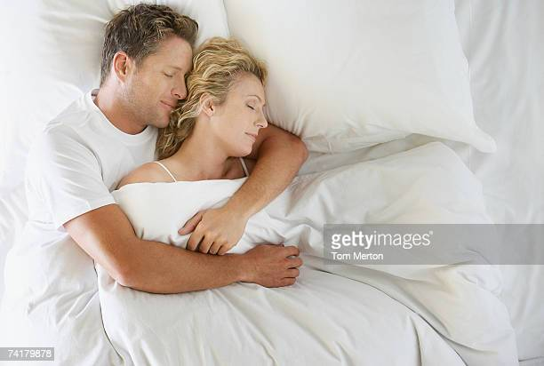 man and woman snuggling in bed asleep - couple sleeping stock pictures, royalty-free photos & images