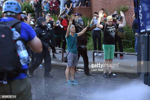 """Man and woman stand in front of police water cannons being used to disperse crowds during the """"Welcome to Hell"""" protest march on July 6, 2017 in..."""