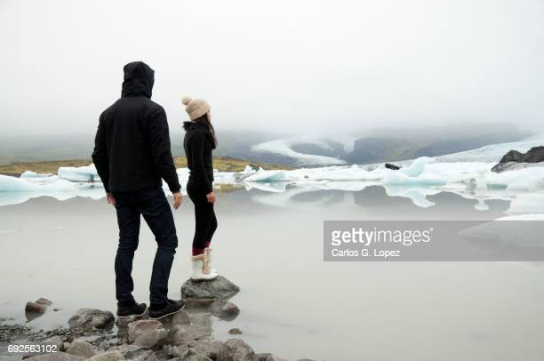 Man and woman stand on edge of glacier lake