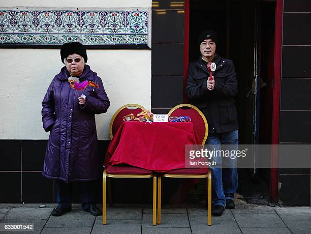 A man and woman stand outside their restaurant during the Chinese New Year celebrations to mark The Year of the Rooster on January 29 2017 in...