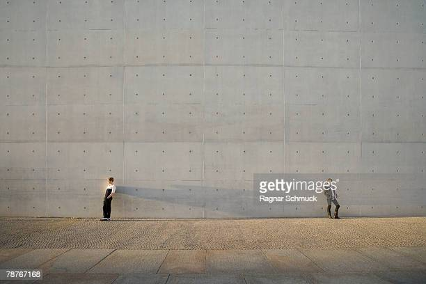 a man and woman standing against a wall - 分離 ストックフォトと画像