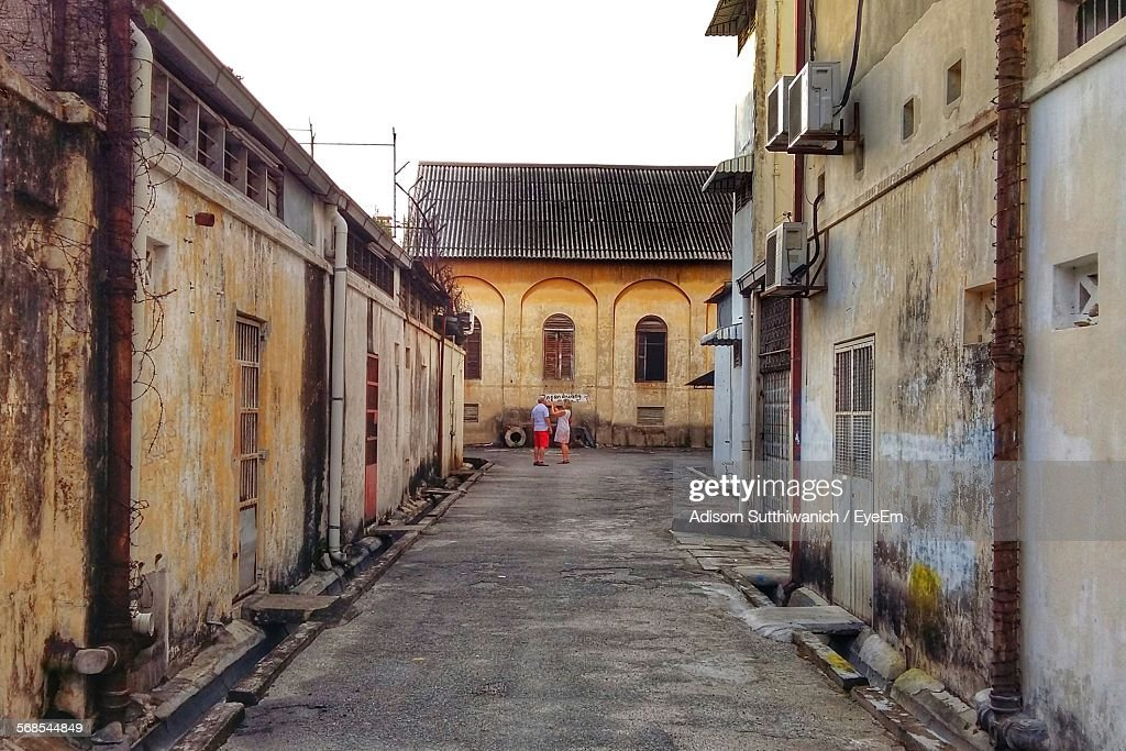 Man And Woman Standing Amidst Houses In Old Town : Stock Photo