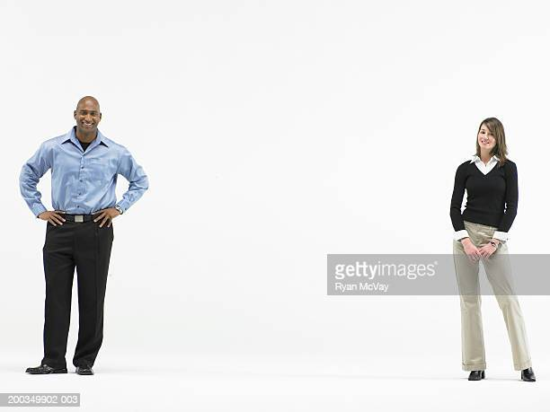 Man and woman standing apart, smiling, portrait