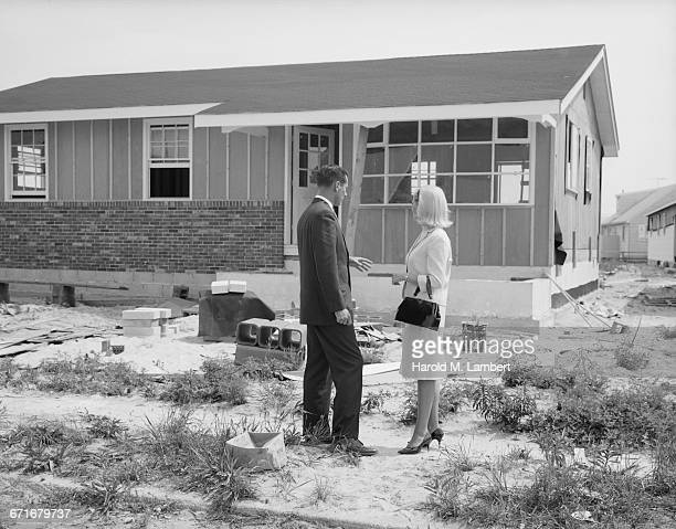 man and woman standing at construction site - {{ contactusnotification.cta }} stock pictures, royalty-free photos & images