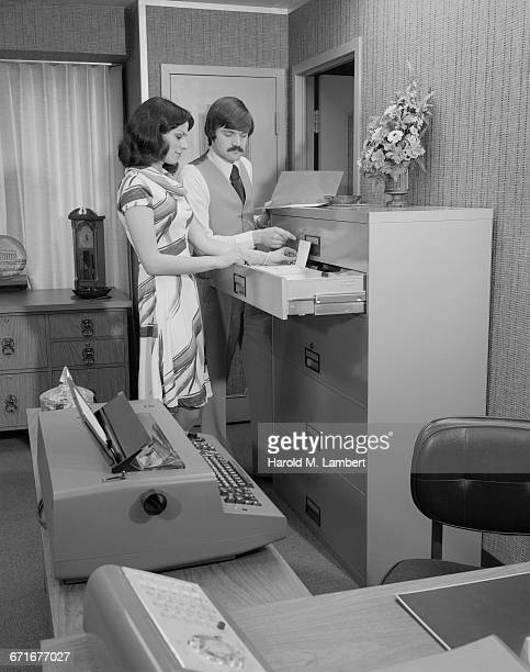 Man And Woman Standing At Copier Machine