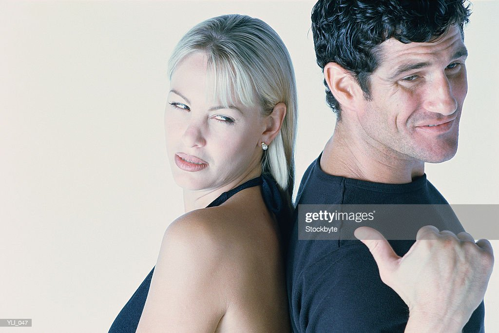 Man and woman standing back to back; man pointing to woman with thumb : Stock Photo