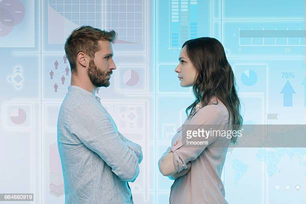 Man and woman standing face to face, data on graphical screen behind them