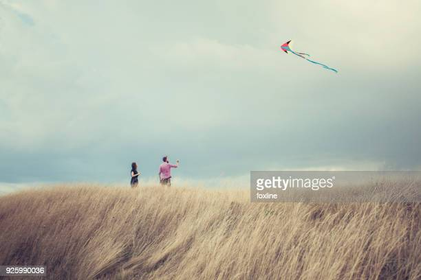 Man and woman standing in a field flying a kite