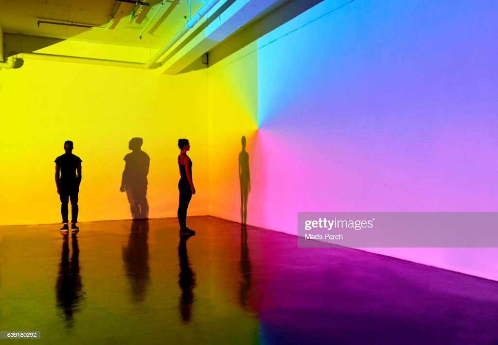 man and woman standing in a gallery space with colourful walls : Stock Photo