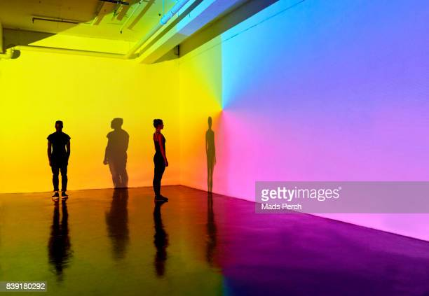 man and woman standing in a gallery space with colourful walls - actuación conceptos fotografías e imágenes de stock