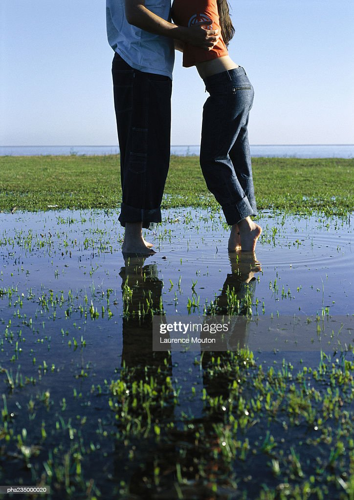 Man and woman standing in a puddle on grass by water. : Stockfoto