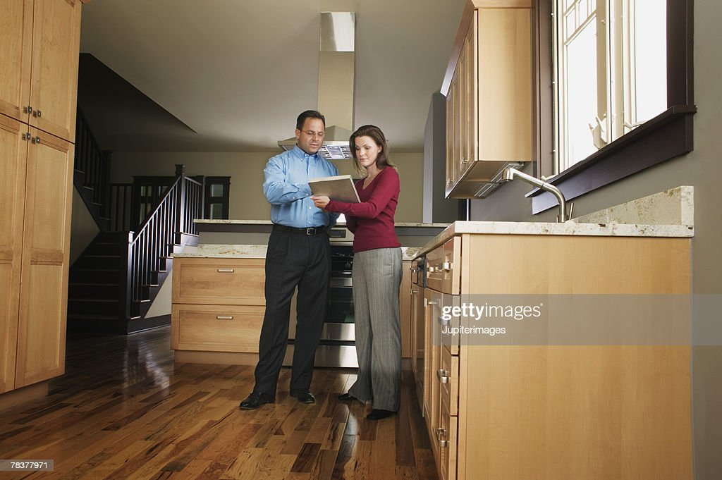 Man and woman standing in kitchen reading document : Stock Photo