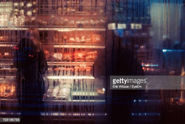 Man And Woman Standing In Store Seen Through Wet Glass During Monsoon