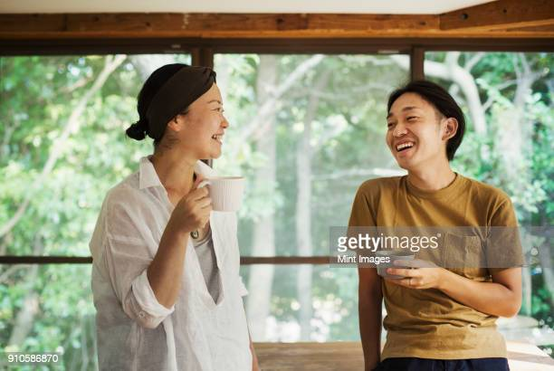 man and woman standing indoors, holding coffee mugs, looking at each other, smiling. - 30代 ストックフォトと画像