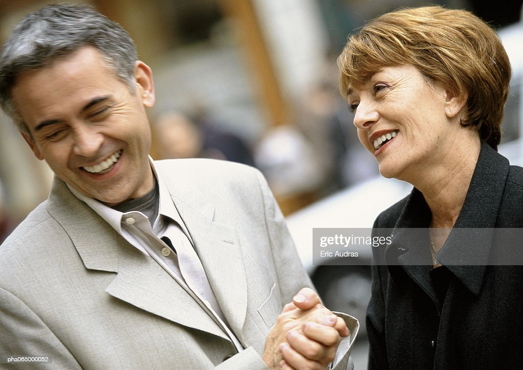 Man and woman standing laughing together, woman looking at man, close up. : Stock Photo