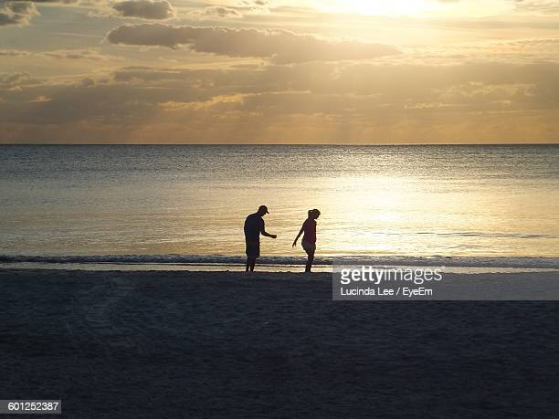 man and woman standing on beach against cloudy sky during sunset - lucinda lee stock photos and pictures