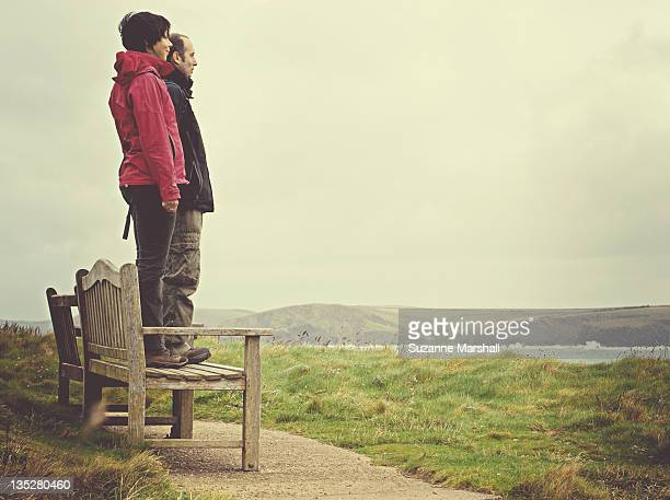 man and woman standing on bench looking out to sea - side by side stock photos and pictures