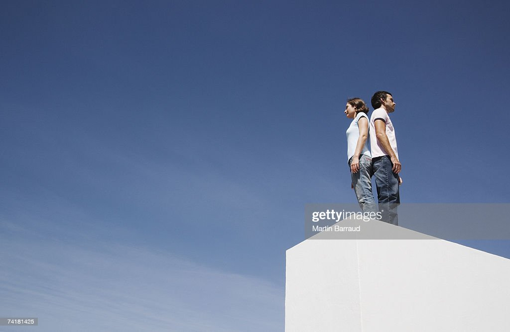 Man and woman standing on box back to back outdoors with blue sky : Stock Photo