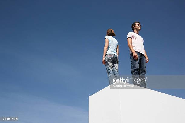 Man and woman standing on box back to back outdoors with blue sky