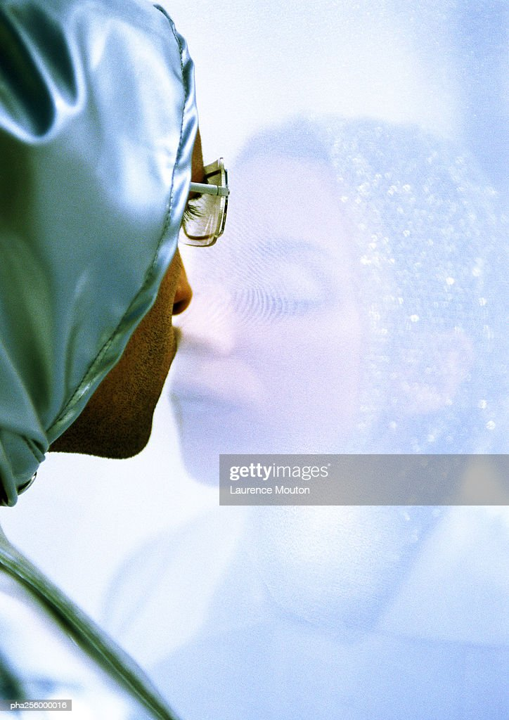 Man and woman standing on each side of transparent screen : Stockfoto