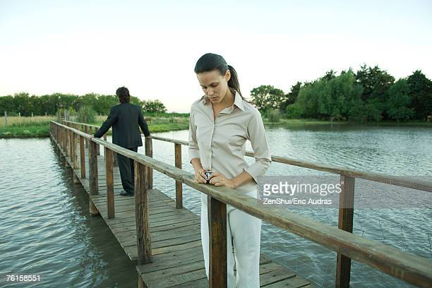 Man and woman standing on footbridge, looking away from each other