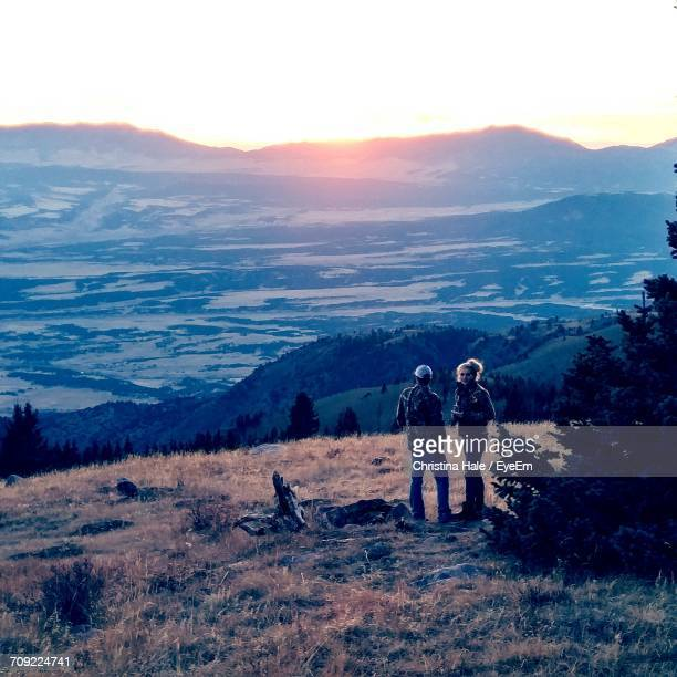 Man And Woman Standing On Mountain Against Sky During Sunset