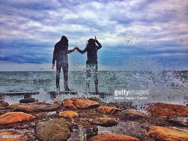 Man And Woman Standing On Rocks At Sea Shore Against Cloudy Sky
