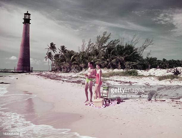 Man and woman standing on shoreline with lighthouse in background USA