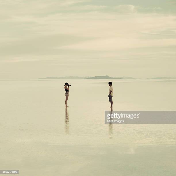 Man and woman standing on the flooded Bonneville Salt Flats, taking photographs of each other at dusk.