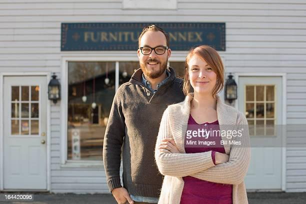 Um homem e mulher em pé fora de uma loja online em uma rua. Um cou