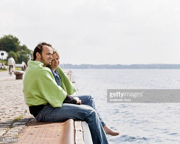 Man and woman stare out at a lake