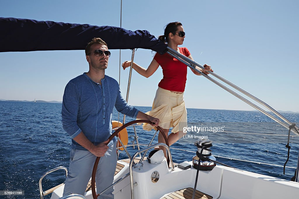 Man and woman steering yacht, Dalmatia, Adriatic sea : Stockfoto