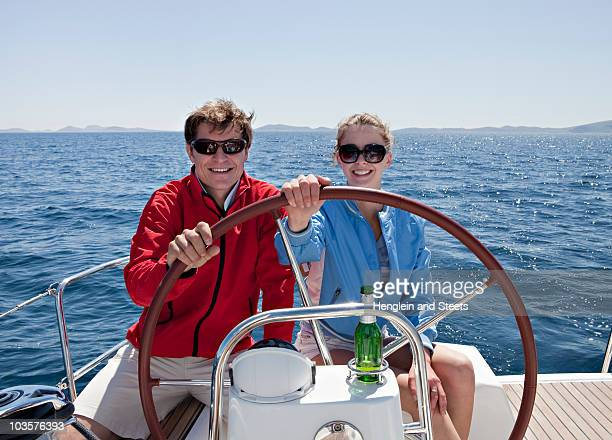 Man and woman steering yacht