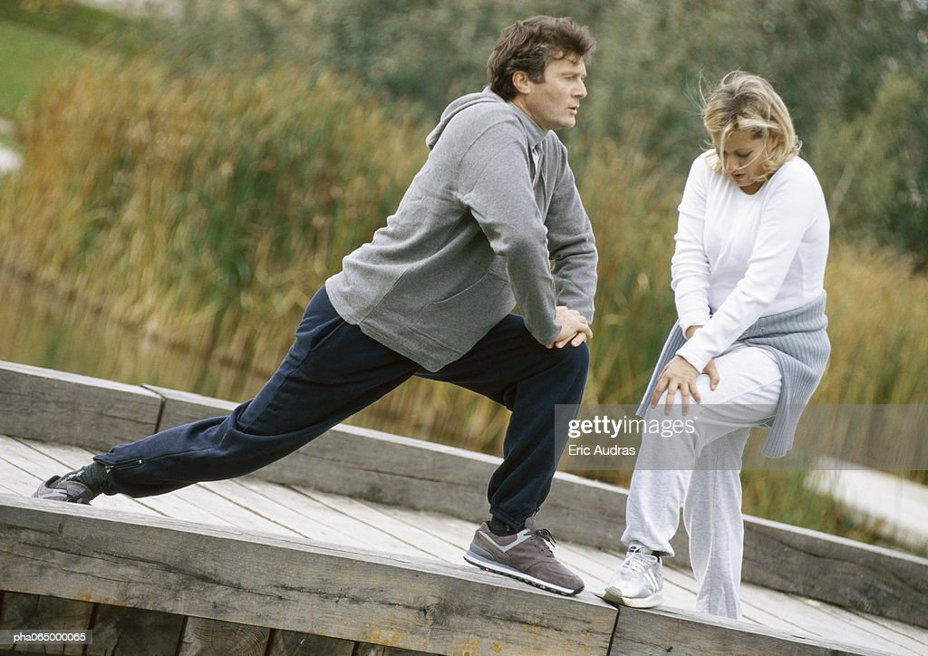 Man and woman stretching legs together on wooden walkway : Stockfoto