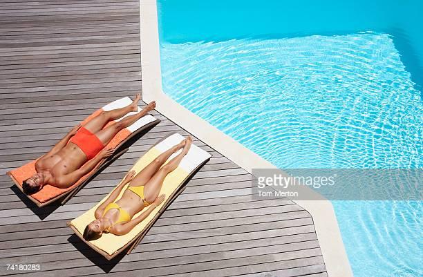 Man and woman sunbathing on pool deck