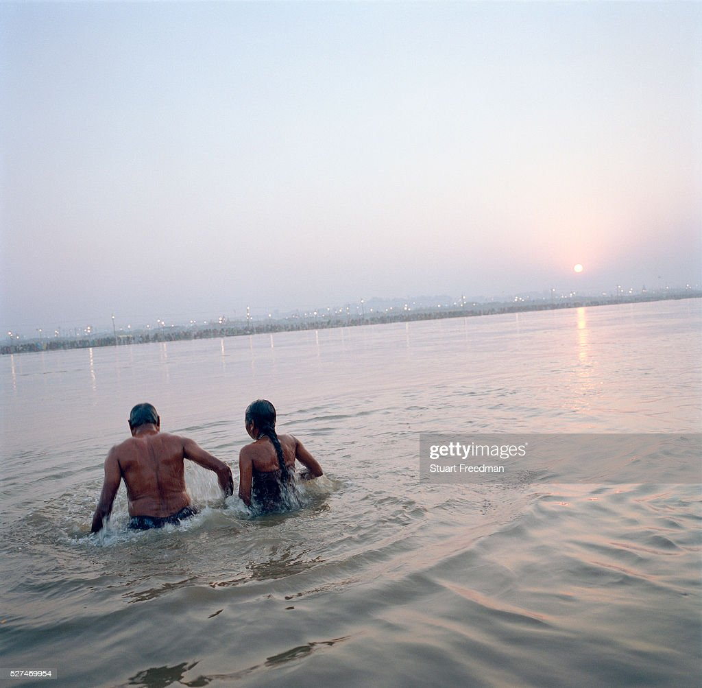India - Allahabad - A man and woman take a ritual bath : News Photo