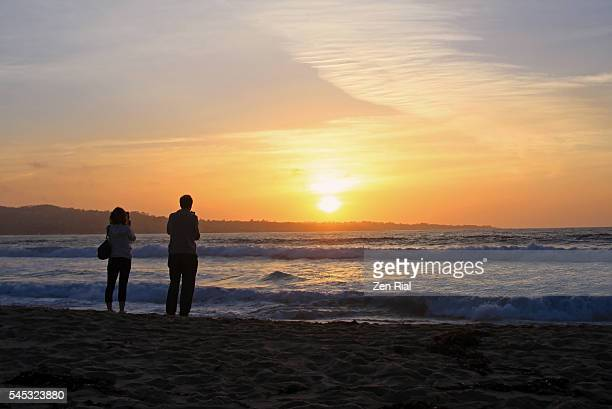 Man and woman takes photos of sunset in Monterey Beach, California