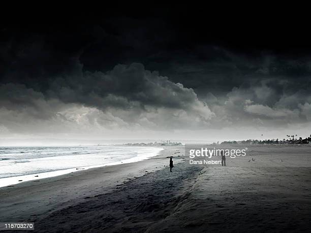 man and woman taking photos on beach before storm - calm before the storm stock pictures, royalty-free photos & images