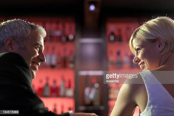 Man and woman talking at a bar.