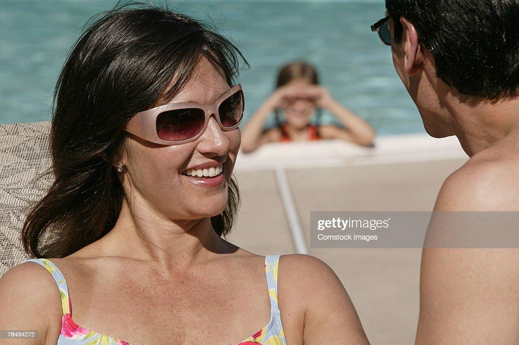 Man and woman talking at pool : Stockfoto