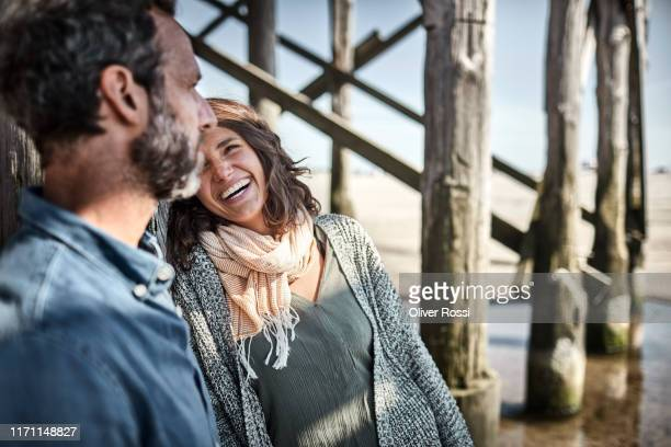 man and woman talking at stilt house on the beach - travel stock-fotos und bilder
