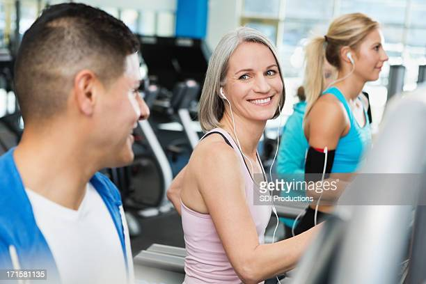Man and woman talking in gym on treadmills while exercising