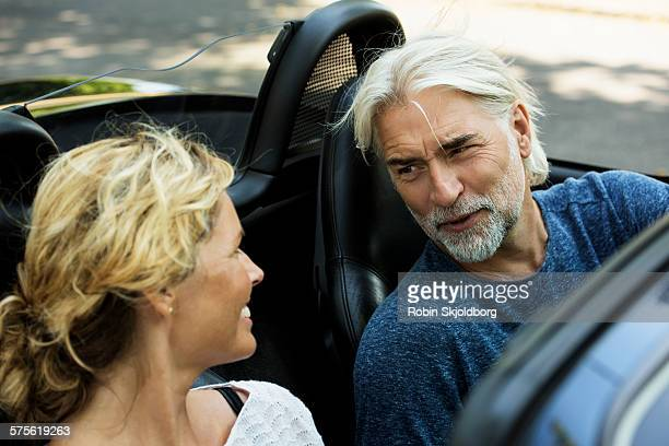Man and Woman talking in open car