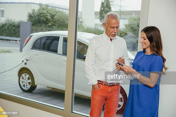 Man and woman talking while charging electric car, woman holding key